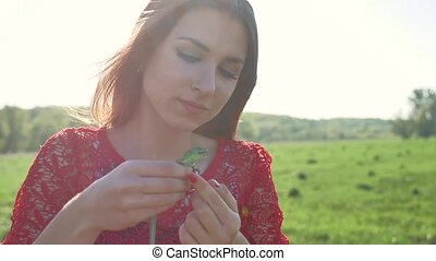 The girl is holding a lizard. Girl in nature holds a green...