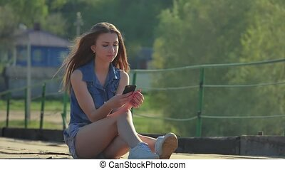 The girl is holding a smartphone. Internet girl in...