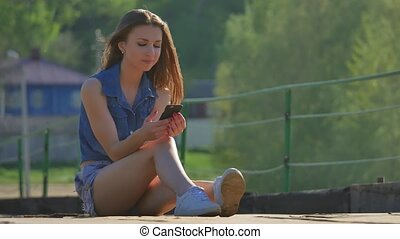 The girl is holding a smartphone. Internet girl outdoor in...