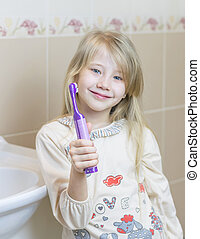 The girl is holding an electric toothbrush in her hand.