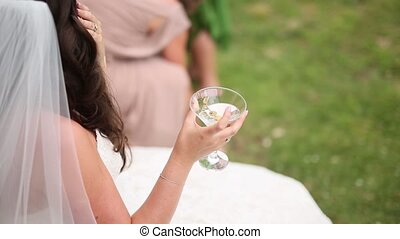 The girl is holding glass with martini cocktail and olives.
