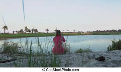 The girl is looking at game on golf course at dusk, makes...