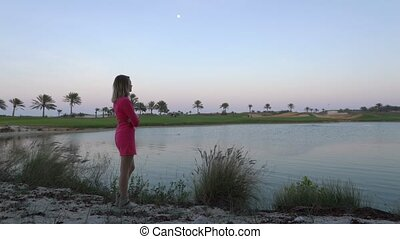 The girl is looking at game on golf course at dusk. Woman...