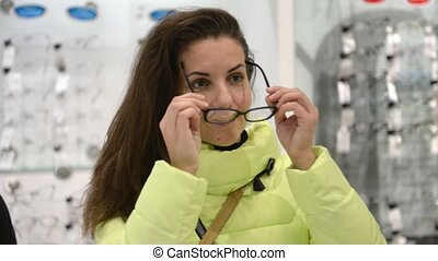 The girl is measuring the glasses in the store. The girl is...