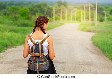 the girl is on the road with a backpack