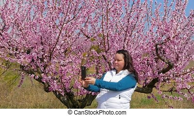 The girl is photographed against the background of a blossoming tree.