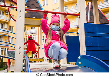 The girl is playing on the playground during quarantine