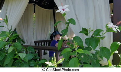 The girl is resting in the chantry on the beach. A young woman looks into her phone and writes sms, enjoying the rest at the hotel. Beautiful bush with white flowers in the garden.