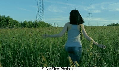 The girl is running across the field. Slow motion
