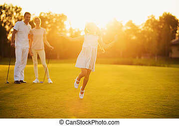 The girl is running against the sunset. Her parents are standing with golf clubs in their hands behind her