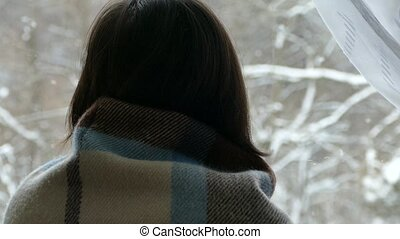 The girl is sitting by the window in winter. A girl looks through the window to the winter forest.
