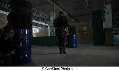 The girl is sitting in ambush - The team plays airsoft in an...