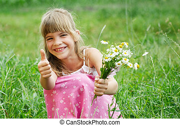 The girl is sitting in the grass and smiling
