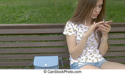 The girl is sitting in the park, on the bench. Looks sms on the smartphone and does not know that her wallet was stolen. The thief pulled out the purse from her purse.