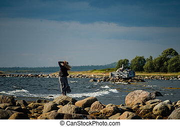 The girl is standing in a dress on the shore of the White Sea