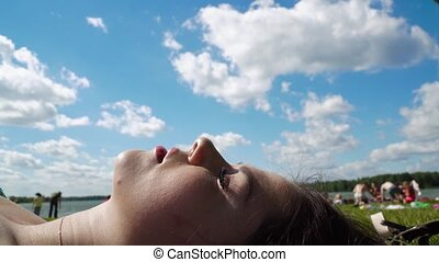 The girl is sunbathing on the city beach, where there are many other people. Face of a girl close-up in the center of the frame