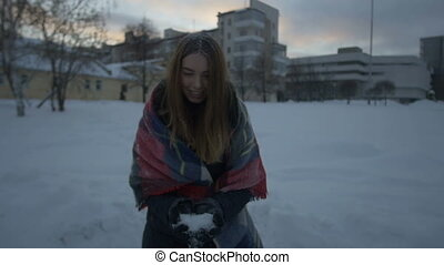 The girl is throwing snow in the street