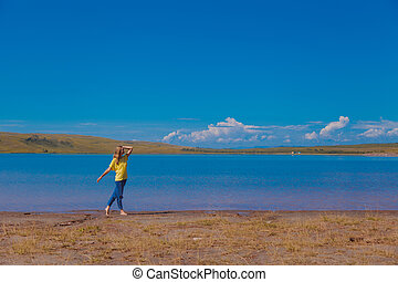 the girl is trampling in the water near the river. a child plays by the pond