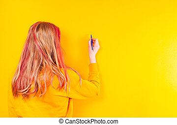 The girl is trying to leave a message on the wall