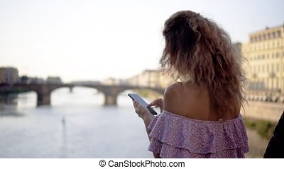 The girl is typing a message on the smartphone