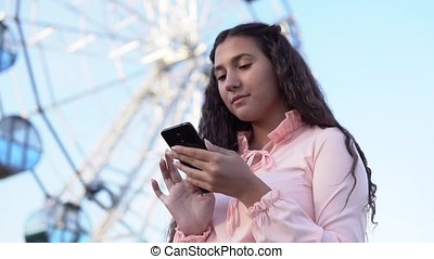 the girl is using a smartphone standing near the big Ferris wheel. slow motion