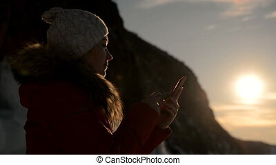 The girl is using the smartphone at sunset.