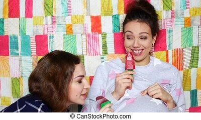 The girl is visiting a pregnant friend. Beautiful young women talk, laugh and eat ice cream.