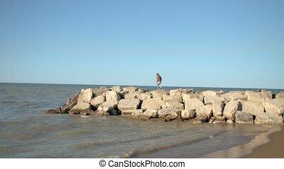 The girl is walking along the rocks near the sea.