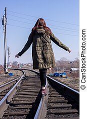 The girl is walking on the railway in front. Rear view.