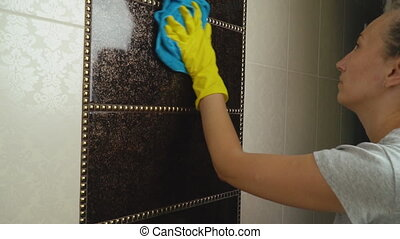 the girl is wiping the tile - a girl in yellow gloves wipes...