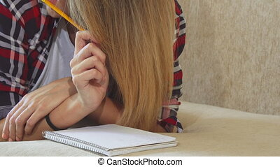 The girl is writing in her notebook