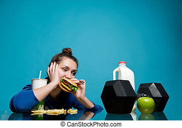 the girl lazily chews a burger and looks at the dumbbell, a bottle of milk and an apple