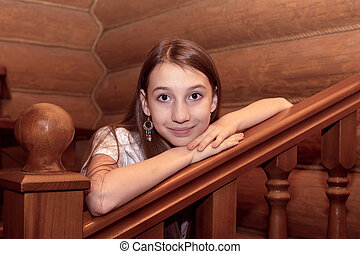 The girl leans on a wooden ladder in a log house.