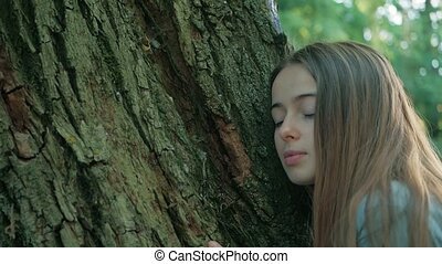 the girl listens to a tree, leans her ear against him. human and nature. enviroment protection