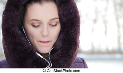 The girl listens to music and snow falls