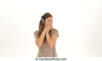 The girl listens to music on headphones and slowly dances.