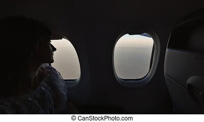 The girl looks and admires from the window of the plane....