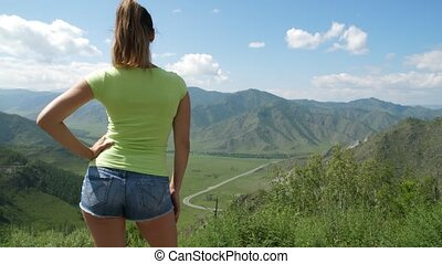 The girl looks at the amazing mountain landscape. Girl in...