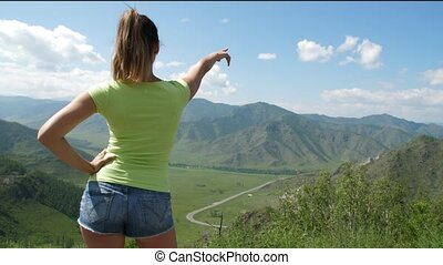 The girl looks at the amazing mountain landscape. woman...