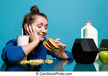 the girl looks at the burger with a smile, and in front of her lies a dumbbell