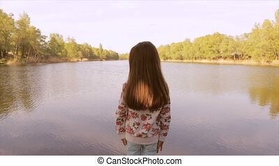 The girl looks at the lakes with her hands on her waist -...