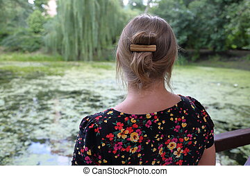 The girl looks at the pond