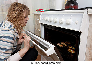 The girl looks in an oven at ready pies