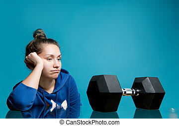the girl looks in frustration and longing at the big dumbbell lying in front of her