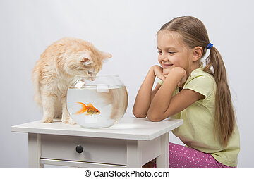 The girl looks like a cat wants to catch the goldfish