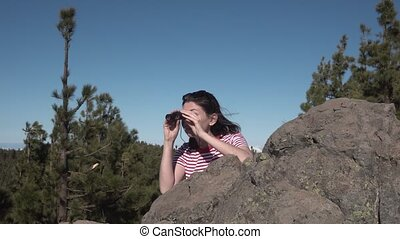 girl looks through binoculars and hides