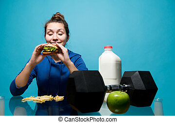 the girl looks with anticipation at the burger, and next to her lies a dumbbell, a bottle of milk and apple