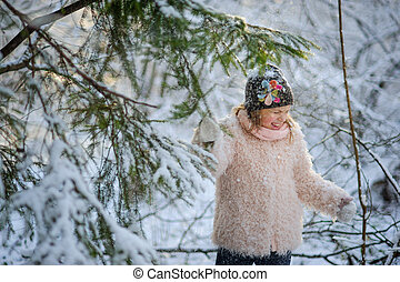 The girl of 8-9 years to shake on herself snow from a fir-tree.