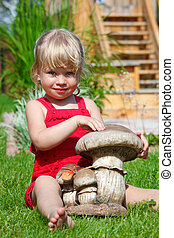 The girl on a lawn sits with a toy mushroom