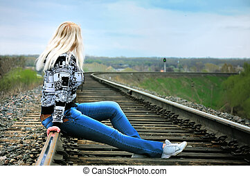 The girl on rails - The girl sits on rails; green light of a...